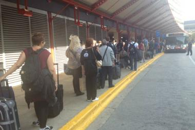 Travelers wait for the Blue Line shuttle line Monday at O'Hare Airport.