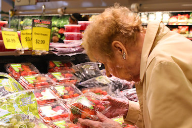 A senior inspects a package of strawberries at Mariano's.  The chain currently has 13 open stores in Chicago and suburbs and hopes to eventually have 30 Mariano's stores in the Chicago market, growing at a rate of 5 per year.