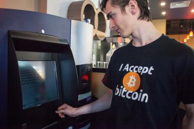 "Gabriel Scheare uses the world's first Bitcoin ATM on Oct. 29 at Waves Coffee House in Vancouver, British Columbia. Scheare said he ""just felt like being part of history."""