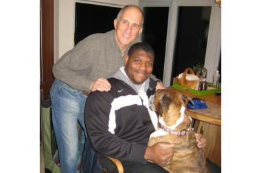 Bob Sperling poses with Laken Tomlinson and the Sperling family dog, a boxer named Brady. Sperling was a crucial figure during Tomlinson's recruitment to Duke University's football team. Tomlinson, who was introduced to the Sperlings in eighth grade, has become like another member of the family.