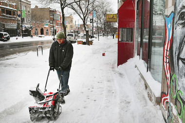 Mike Reyes clears snow on Division Street in Humboldt Park.