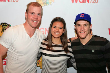 High school freshman Liz Spurlock has custom-painted Blackhawks logos on Converse All-Stars shoes. Here Spurlock is shown with two of her favorite players, Bryan Bickell (l.) and Andrew Shaw.