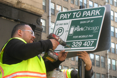 CPM workers install a ParkChicago sign in the South Loop.