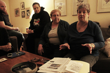 Jan Fowler (r.) sits with her neighbors Tuesday night to discuss parties at the Ridge House, a home taken over by squatters who say they're doing the community good.