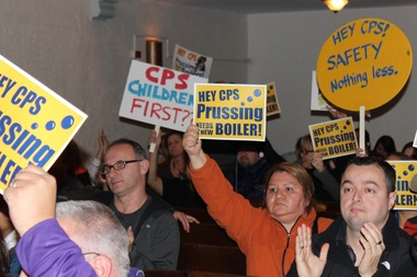 Many Prussing parents waved signs and placards denouncing CPS' response to the carbon monoxide leak at the Jefferson Park school throughout the meeting.