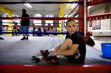 Eleven-year-old Felix Gonzalez laces his shoes and wraps his wrists before his training session at the Chicago Youth Boxing Club.