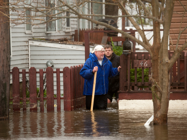 <p>Residents stand in flood waters and survey the damage in Breezy Point on Tuesday October 30th, 2012.</p>