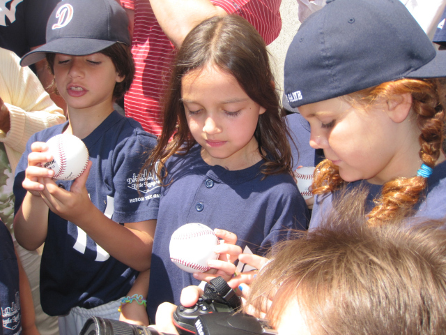 <p>Downtown Little League players examine freshly autographed baseballs.</p>