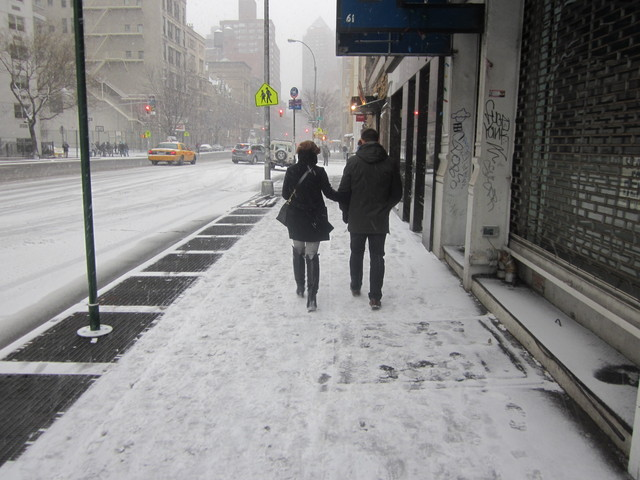<p>A couple walks along Third Avenue in the East Village.</p>