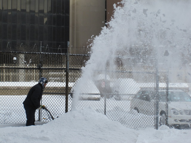 <p>A worker uses a snow-blower to clear a path along East 36th Street.</p>