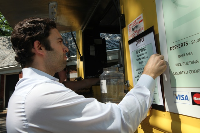 Pera food truck owner Burak Karacam hangs the truck's liquor menu in June 2011.