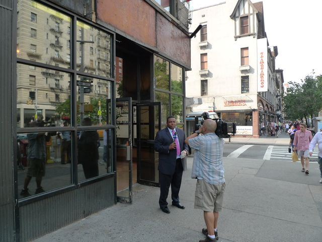 A news crew outside H&H Bagels reporting on the store's closure.