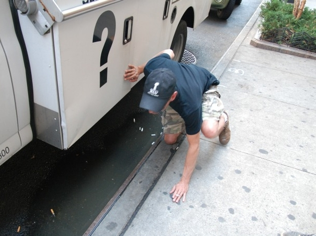 Todd Koplin takes a whiff of the once-smelly puddle.