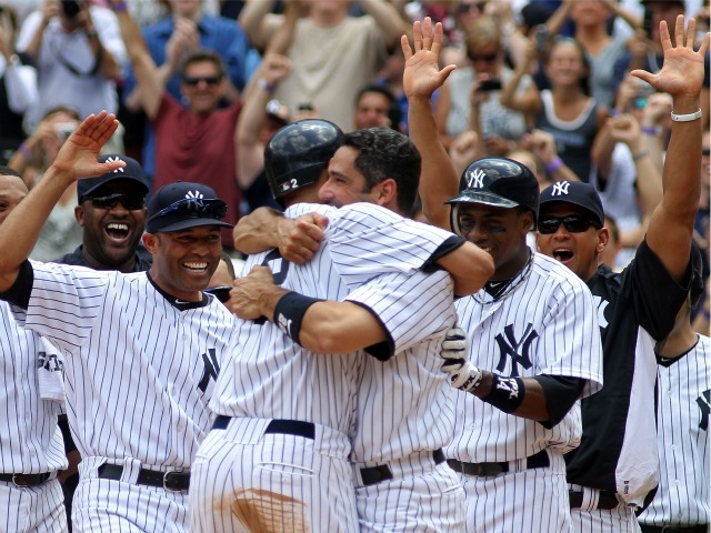Derek Jeter celebrates at home with teammates Jorge Posada, Mariano Rivera, Alex Rodriguez and Curtis Granderson after hitting a solo home run in the third inning for career hit 3000 while playing against the Tampa Bay Rays at Yankee Stadium on July 9, 2011.