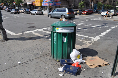 Garbage pours out of a garbage can over the weekend in Inwood.