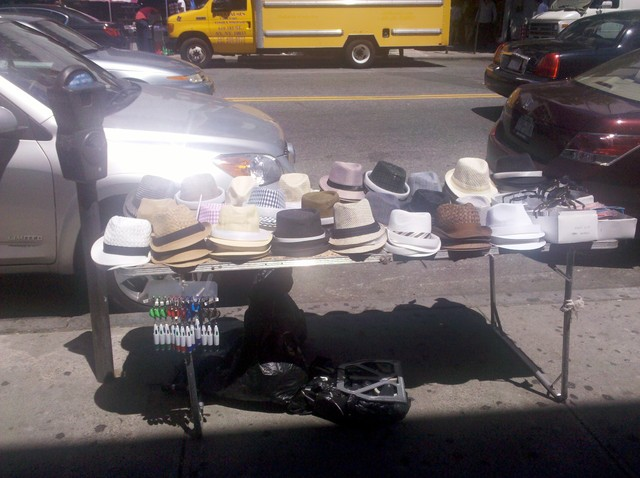 A vendor sells hats on St. Nicholas Avenue.