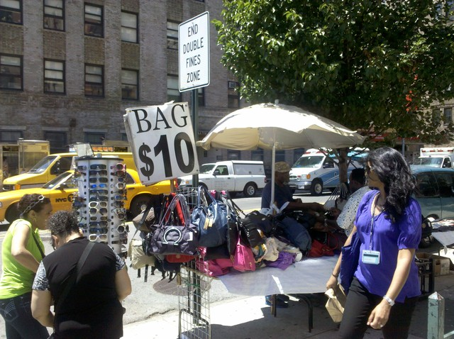 A vendor sells $10 handbags on Broadway and 168th Street.
