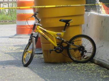 A child-sized yellow bike remained at the scene after police say a 12-year-old was hit by a car.