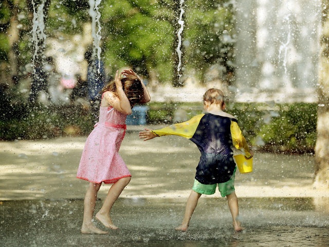 Kids cool off in a fountain as jets spray water upwards at Battery Park.