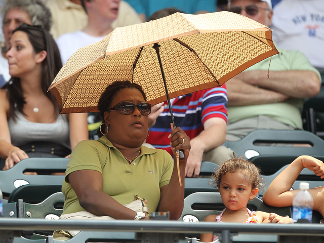 A fan tries to stay cool to beat the heat during the game between the Mets and Cardinals at Citi Field.