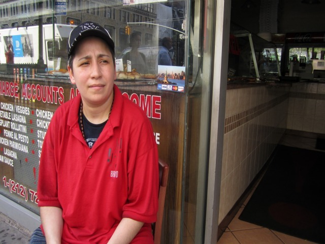Sandy Reyes, 40, an employee at Bravo Pizza, sits in front of the darkened shop. Several stores on the northwest corner of 7th Avenue and 14th Street lost power the afternoon of Friday, July 22, 2011.