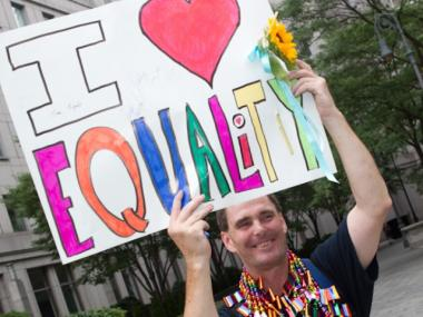 Same-sex marriage supporter holds a sign outside the city clerk's office on July 24, 2011, the first day of legal same-sex marriage in new York.