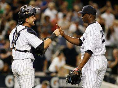 Francisco Cervelli (left) congratulates teammate Rafael Soriano after beating the Orioles at home on July 30, 2011.