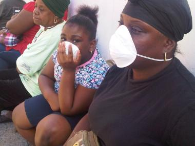 Celeste Hollman sat across the street from her building on St. Nicholas and 151st Street with her daughter Friday. They put on the masks because Hollman was concerned about the strong odor of gas in the air.
