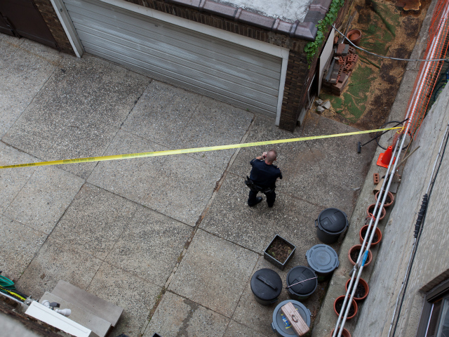 Police investigate the crime scene where a police officer is accused of raping a woman behind a row of homes on Park Terrace West Aug. 19, 2011.