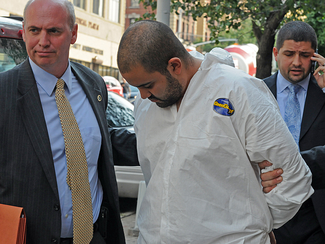 Officer Michael Pena (in white suit) was led out of the 34th Precinct on August 19, 2011.