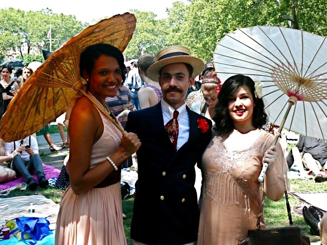 A gentleman in a double- breasted navy blue blazer and hard straw boater with two 30s-inspired ladies
