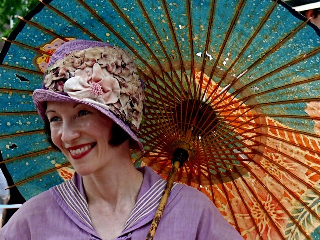 Heidi Rosenau, an avid vintage collector and historian is wearing a lavender nautical ensemble with a matching cloche hat asymmetrically decorated with silk flowers. Her parasol is an antique from the jazz era.