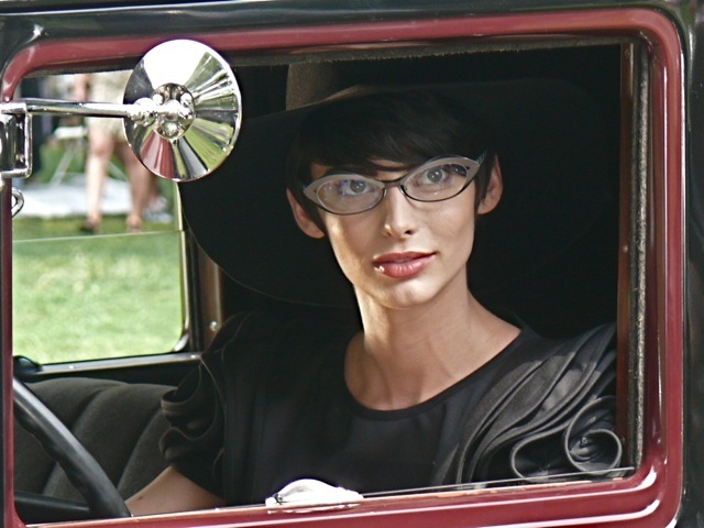 Posing in an antique car wearing a 30s style black ruffle shoulder dress a wide brimmed hat and Alain Mikili eyewear
