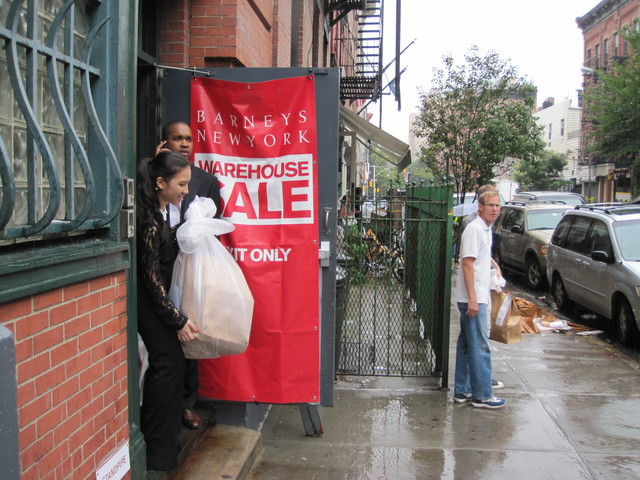<p>Shoppers brace their purchases for the rain after shopping at the Barneys Warehouse Sale.</p>