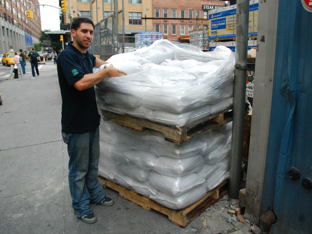 Phil Dean, at Prince Lumber in Chelsea, loads sandbags off onto a skid on Aug. 26.