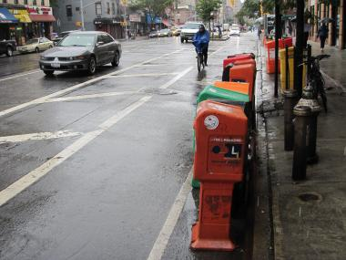 A cyclist goes past eleven boxes that somehow ended up in the Eighth Avenue bike lane.