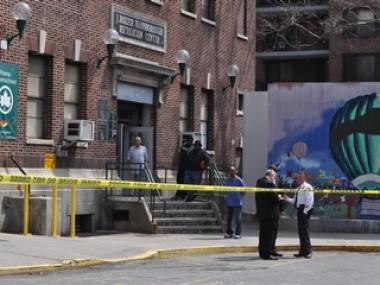 People look on as police investigate a shooting outside the J. Rozier Hansborough Recreation Center on 135th Street in Central Harlem on Monday, April 11, 2011.
