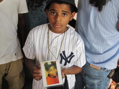A young mourner holds a picture of Tayshana Murphy.