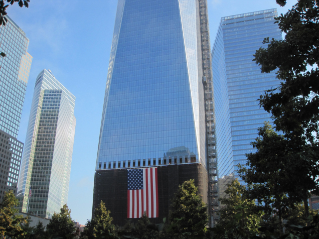 One of the rising World Trade Center buildings is visible from the 9/11 Memorial.