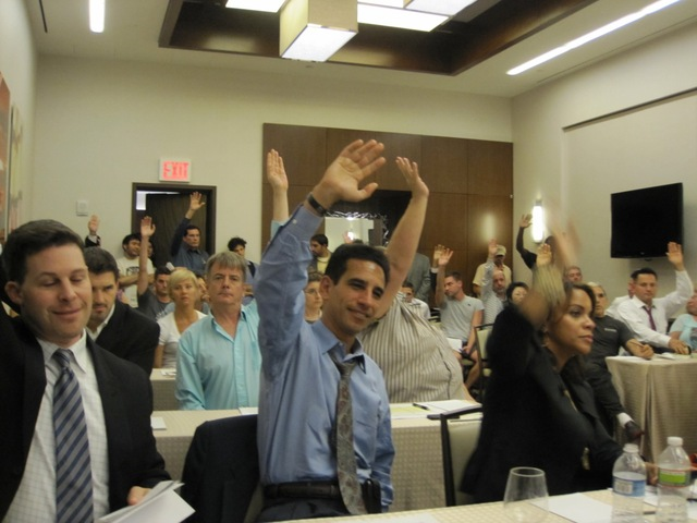 Supports of Boxers HK raise their hands at the Community Board 4's licenses and permits meeting.