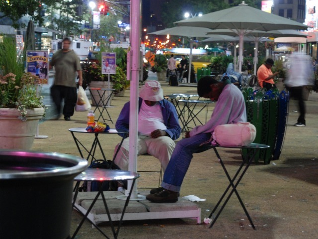 Two men sleep slumped in chairs in the plaza space directly in front of Macy's Herald Square, Wed. Sept. 14.