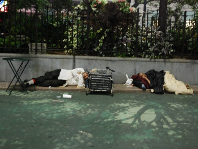 A man and woman sleep in the plaza space directly in front of Macy's Herald Square, Wed., Sept. 14.