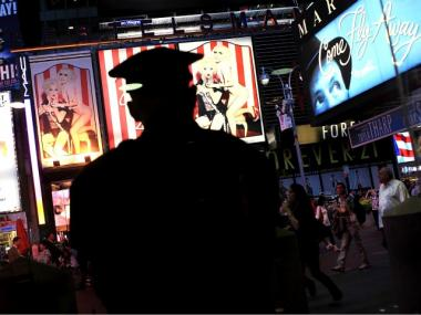 A New York City police officer stands watch in Times Square May 3, 2010 in New York City. Published reports this evening say authorities have arrested a suspect in the attempted car bombing in Times Square on May 1. The reports say a U.S. citizen of Pakistani descent was arrested, though the location has been variously reported as on Long Island and at JFK airport.