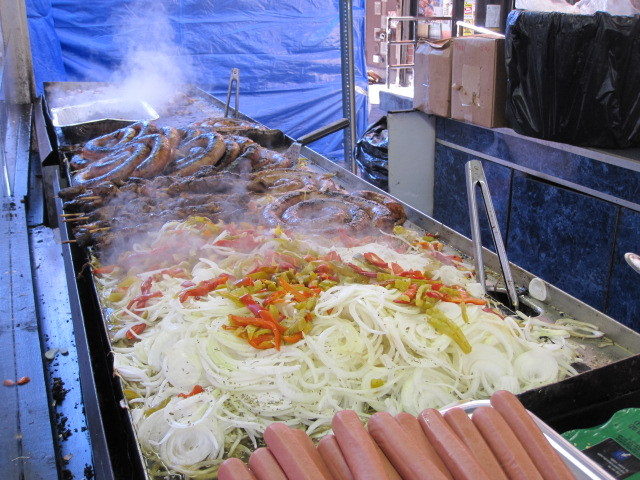 Sausages, onions and peppers cook at the San Gennaro festival on Fri., Sept. 16, 2011.