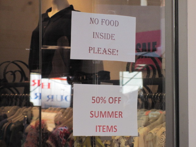 A sign in he window of a Mulberry Street clothing store warns against bringing food inside.