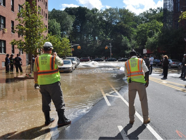 Workers watch as water is pumped onto the street.