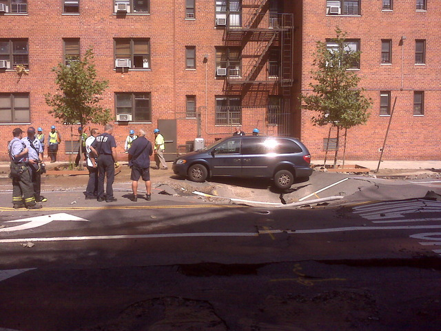 A minivan perches precariously on 106th st near Central Park West, as emergency personnel attempt to remove it to excavate the broken water main beneath, Sept. 19, 2011.