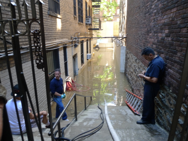 Crews pumped water out of a flooded courtyard  at 467 Central Park West after a water main break.