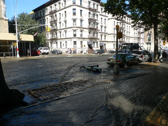 A water rushing down Central Park West after a water main break toppled a motorcycle parked on the street.