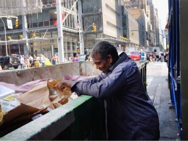A man looks through a trash dumpster on September 14, 2011 in New York City. New Census Bureau figures released today reveal that 3.08 million people in New York State were living in poverty in 2010, or 16 percent, up from 15.8 percent in 2009.